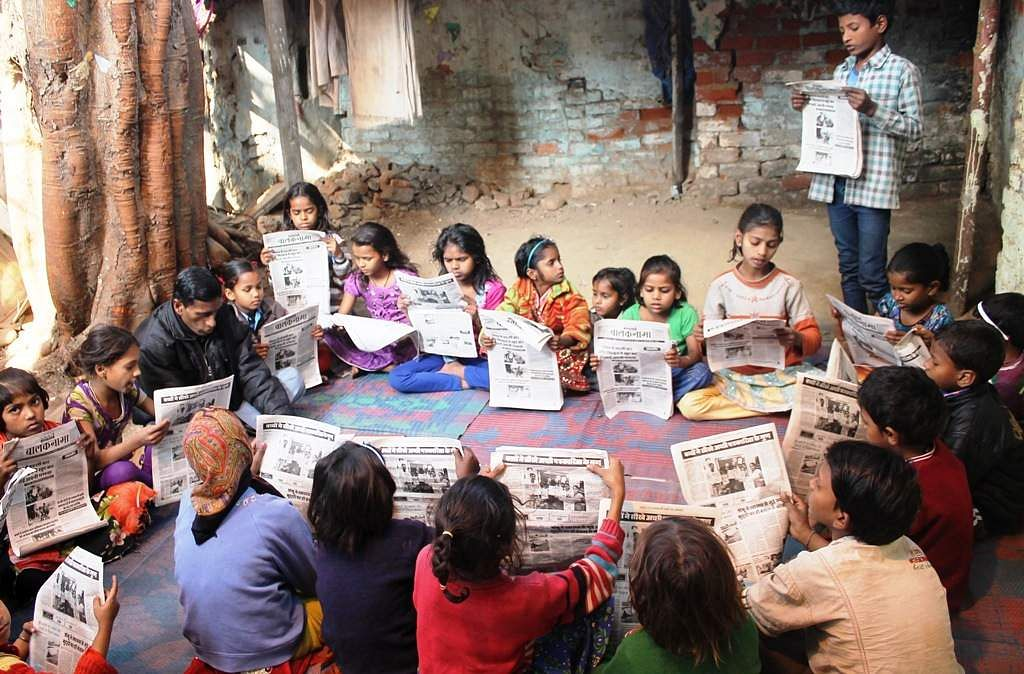 Children read a copy of their newspaper