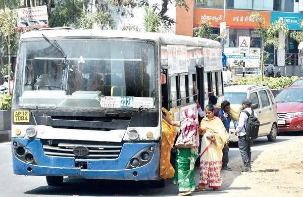 Women risk their lives by travelling on the footboard of the bus