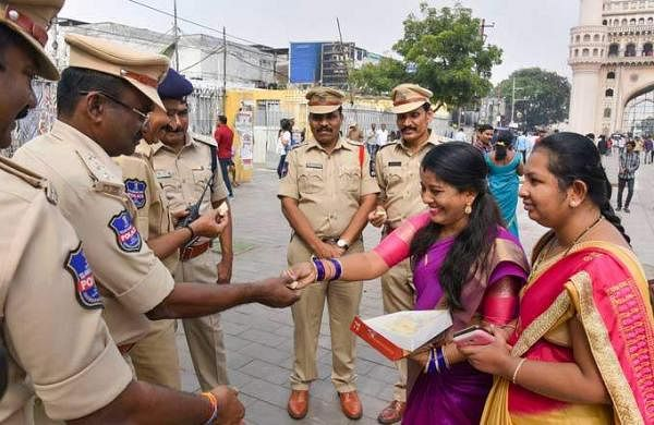Women offer sweet to policemen after four accused in the in the gang rape and murder of a 25-year-old veterinarian were killed in an encounter | Pic: PTI