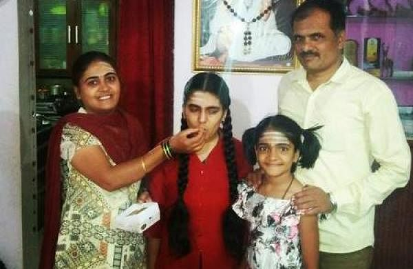 Basamma with her parents and sister celebrating her success by feeding sweets