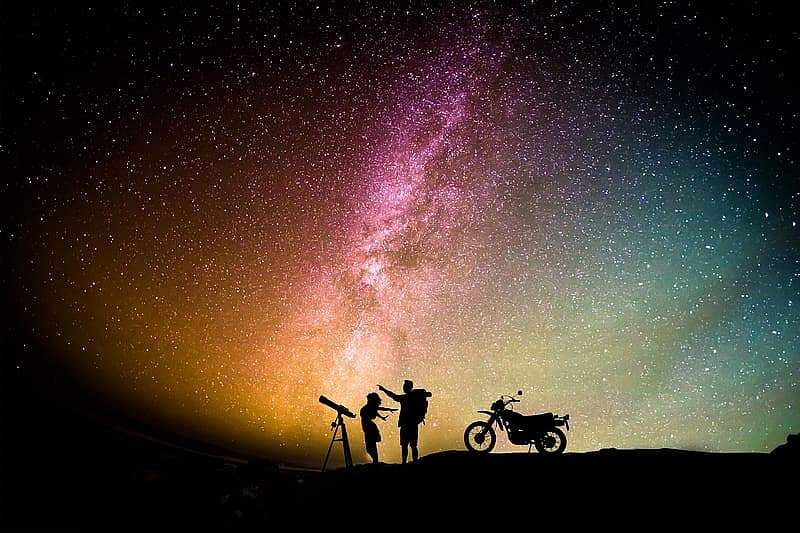 silhouette-photo-of-man-and-woman-standing-between-telescope-with-stand-and-motorcycle