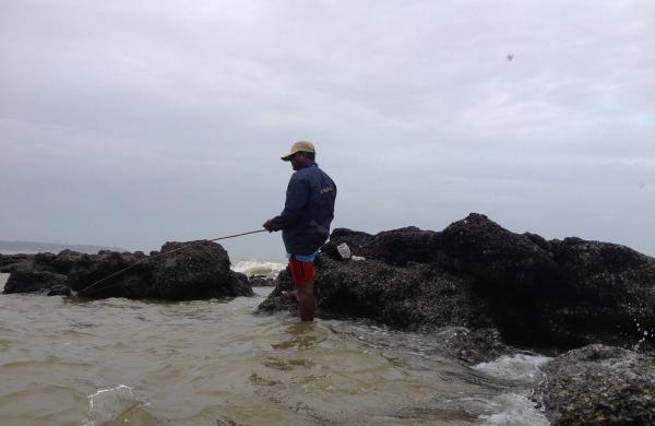 Fisherman_catching_fish_in_Vainguinim_beach